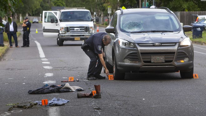 A Springfield police officer gathers evidence at the scene of a bike vs. vehicle crash at Centennial Boulevard and Sixth Street in Springfield on Wednesday morning. [Chris Pietsch/The Register-Guard] - register-guard.com