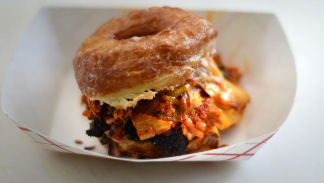The Chonut from Kimchi Smoke Barbecue is a glazed doughnut stacked with   brisket, melted cheddar cheese, and smoked kimchi with Fatboy Bourbon Chipotle Sauce.