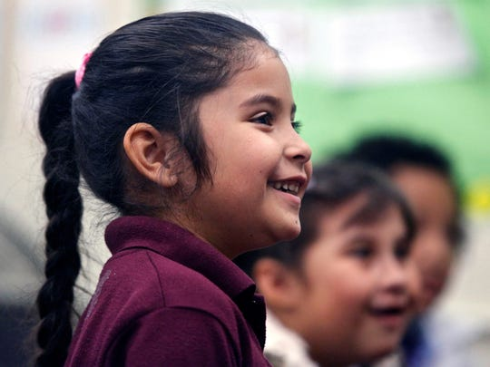 "A little girl smiles as she listens to Congressman Raul Ruiz during his visit to Mecca Elementary School on Thursday. Ruiz returned to the school district that he attended as a child to serve as ""principal for a day."""