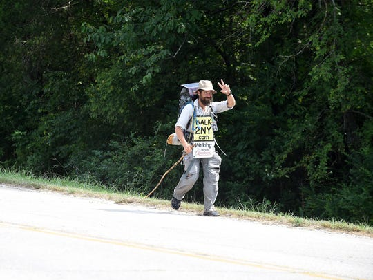 Ryan Ray waves to a passing motorist Tuesday while walking through Flippin.