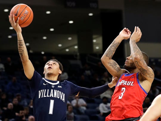 Villanova guard Jahvon Quinerly, left, drives to the basket against DePaul guard Devin Gage during the first half of an NCAA college basketball game Wednesday, Jan. 30, 2019, in Chicago. (AP Photo/Nam Y. Huh)