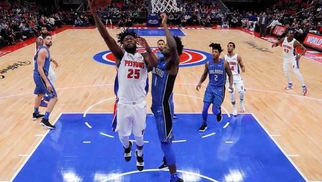 Pistons forward Reggie Bullock (25) drives to the basket against Magic forward Jonathan Isaac (1) in the second half of the Pistons' 114-110 win on Sunday, Dec. 17, 2017, at Little Caesars Arena.