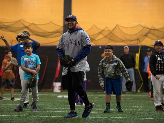 Jose Trevino, a minor league player for the Texas Rangers loughs before pitching a ball to a kid attending the first Trevino Toy Drive and baseball camp in Alice Texas on Saturday, Dec. 16, 2017.