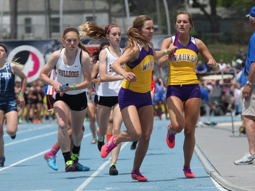 Waukee's Keely Smith takes the baton from Kayla Sabotin in a preliminary heat of the 4x400 relay Friday at the Class 4-A co-ed state track meet at Drake Stadium in Des Moines.