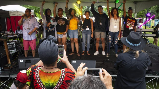 Audience members crowd in for a photograph as the organizers are introduced during The Official Juneteenth Celebration Eugene organized by the Blac Eug, Black-Led Action Coalition, at Alton Baker Park Saturday in Eugene . [Chris Pietsch/The Register-Guard] - registerguard.com