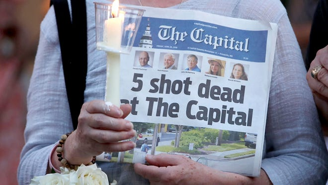 A women holds the Capital Gazette newspaper during a candlelight vigil to honor the 5 people who were shot and killed on June 29 in Annapolis, Maryland.