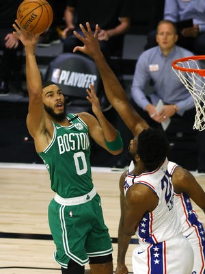 Celtics forward Jayson Tatum shoots over the outstretched hand of Philadelphia 76ers big man Joel Embiid during the first quarter of Game 2 of their playoff series Wednesday in Lake Buena Vista, Fla.
