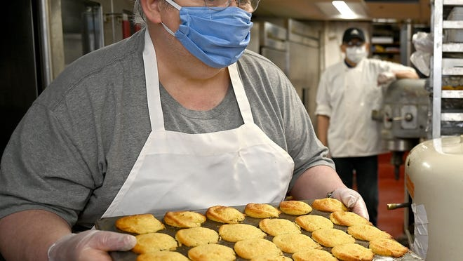 Bill Turner, head baker at Longfellow's Wayside Inn in Sudbury, handles a tray of corn muffins. The inn is doing a meal donation program for delivery for essential workers.