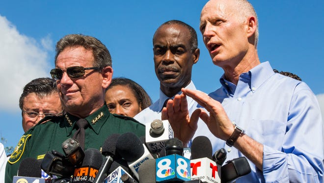 Gov. Rick Scott, alongside Broward CountyÊSuperintendentÊRobert Runcie and Broward County Sheriff Scott Israel, addresses the press during the first media briefing on Thursday, Feb. 15, 2018 outside of Marjory Stoneman Douglas High School in Parkland, Fla.