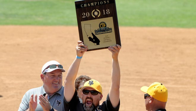 Mike Dagan holds up the championship plaque after Newbury Park won the CIF-SS Division 2 softball title in 2018. Dagan died Friday at the age of 50.