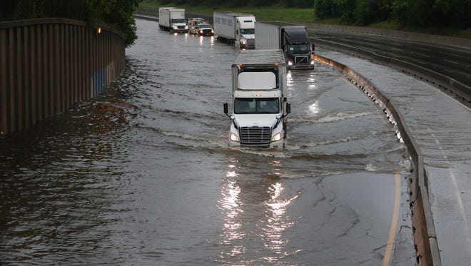 Trucks drive slowly through floodwater on North I-45 at North Main Street as White Oak Bayou comes over its banks, flooding the freeway Monday in Houston. More than a foot of rain Monday in parts of Houston left scores of subdivisions and several major highways underwater, knocked out power to thousands of people and closed schools.