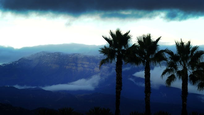Looking north from Oxnard, clouds hang over the mountains during Saturday afternoon's storms.