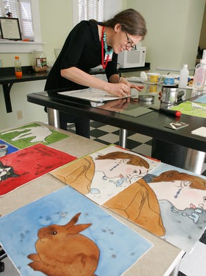 Sophie Knee, a primitive painter, uses the trace monotype technique during a demonstration Thursday at the Bryn Du Art Exhibition. Knee has artwork displayed in the viscosity monotype technique.