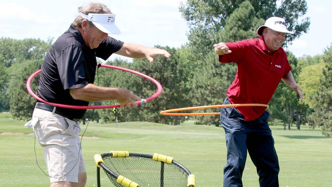 Senior PGA Tour professionals Joey Sindelar, left, and Kirk Triplett have a hula hoop contest Monday afternoon during the youth golf clinic at the Orion Classic at the Country Club of Sioux Falls.