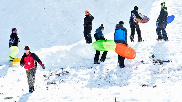 Sledders climb the hill off Norlo Drive, a popular