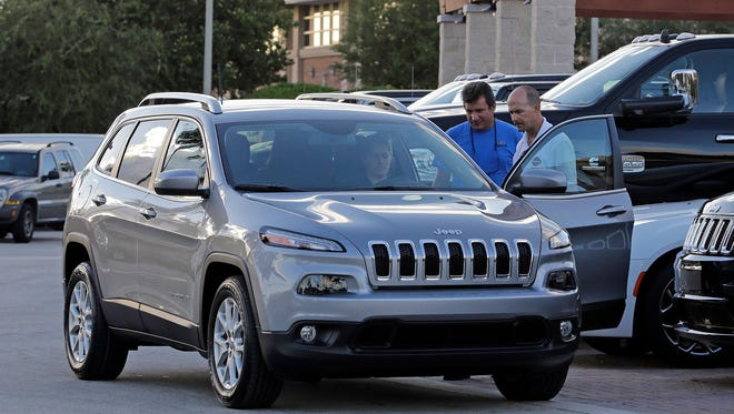Salesman Jerry Camero, right, delivers a 2016 Jeep Cherokee Limited to a customer at a Fiat Chrysler dealer in Doral, Fla., in November.