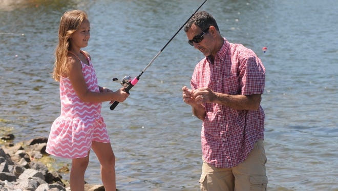 Sam DeLeo baits a hook for his daughter Claire at Sunday's Fishing Derby and Outdoor Expo. The derby wrapped up the weekend-long Granite City Days festival.