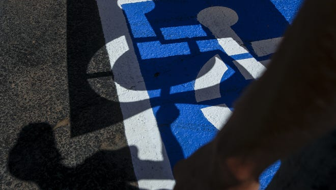Jeff Tetzloff, of Maricopa, pulls away the stencil from the newly painted disabled parking stall at Y-Knot Party & Rentals in Mesa on July 14, 2016. The business is restriping the handicap stalls in their parking lot to meet accessibility requirements outlined by the Americans with Disabilities Act.