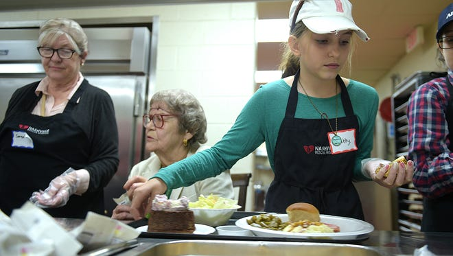 Gabby Jones 11, adds butter to meals at The Nashville Rescue Mission on Christmas Day, Dec. 25, 2016. Gabby and her family have been volunteering on Christmas Day since Gabby was four-years-old.