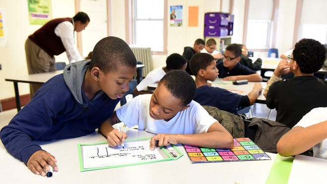 Fourth-grade students Mekhi Walker, 9 and Elijah Warren 9, L-R, work together solving a math problem during a math intervention class taught by Paterson Leadership Academy for Young Men teacher Michae Fede, November 23, 2015.