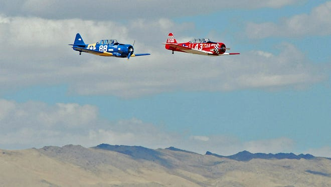 Fallon's Dennis Buehn in the No. 43 T-6 Midnight Miss III is out in front of the John Lomar's No. 88 Radial Velocity during Sunday's Gold Medal Race at the Reno National Championship Air Races.