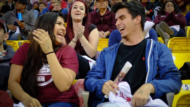 19-year-old NMSU sophomore Gabriella Hengel, originally from El Paso but now an Aggies supporter, and 18-year-old NMSU freshman Alex Killgore, celebrate NMSU scoring during the first quarter of the basketball game against UTEP on Wednesday at the Pan American Center.