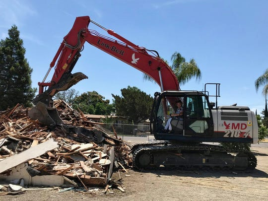 VEAC Executive Director Liz Wynn takes a turn behind the wheel of an excavator to help remove debris during demolition of the previous administration building on Tuesday May 29, 2018.