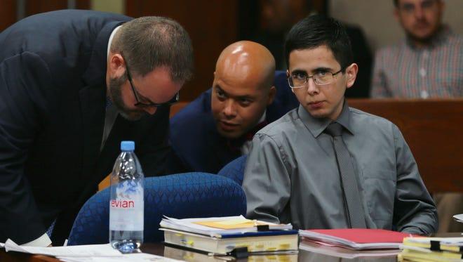 Adrian Garcia listens to his defense attorneys Monday.