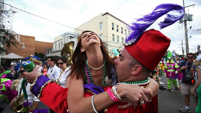 Ginger Colgan dances with a marchers in the Krewe of Thoth parade in New Orleans on March 2.