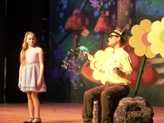 Kade Ebert blows bubbles at Cassandra Kurek who stars in the play as Alice.