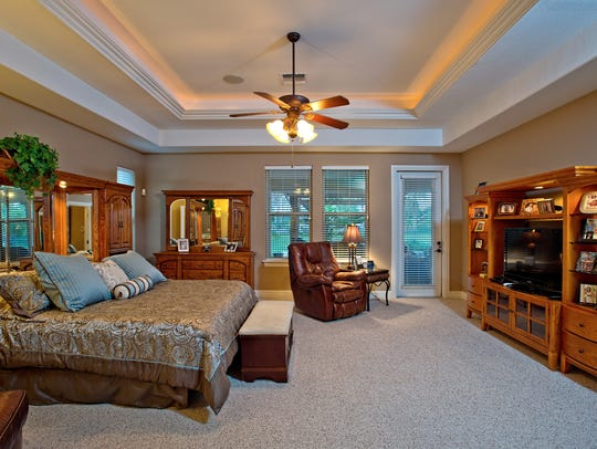 The large master bedroom has a crown molded recessed