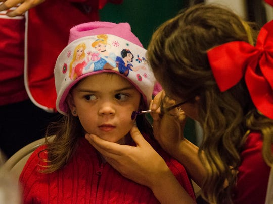 Children get their faces painted at the 12th Annual Olde Fashioned Christmas Festival in the Historic Depot District in Richmond, Ind. on Tuesday, Nov. 29, 2016.