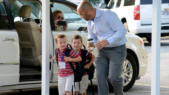 Dr. Jake Long helps twins Calder and Christian Chamberlin to class  during the first day of school at the Mountain Home Kindergarten in August 2015.