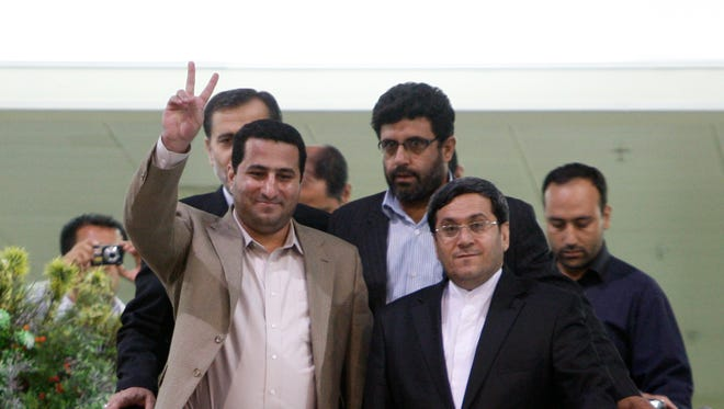 In this July 15, 2010 file photo, Shahram Amiri, an Iranian nuclear scientist, flashes a victory sign as he arrives at the Imam Khomeini airport just outside Tehran, Iran, from the United States.