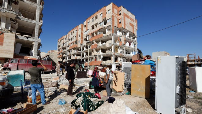 Iranian people collect belongings from damaged buildings after earthquake in city of Sare Pole-Zahab in Kermanshah Province, Iran, Nov. 14, 2017.