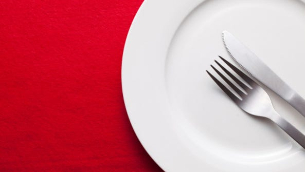 A stock image of a plate, knife and fork against a