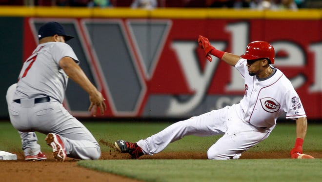 Reds center fielder Billy Hamilton steals second base, beating the tag from Cardinals shortstop Jhonny Peralta.