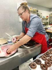 """Sherry Richardson,  owner of Mimi's Donuts and Bakery, Millville,  dips donuts into frosting at her shop.  The business is one of nine independent donut shops on the Butler County """"Donut Trail."""""""