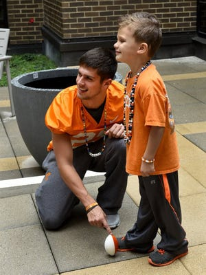 Tennessee kicker Aaron Medley poses for a photo holding the football for oncology patient A.J. Cucksey during a visit to East Tennessee Children's Hospital on Nov. 2, 2015.