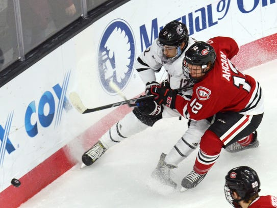 Nebraska Omaha's David Pope, left, and St. Cloud State defenseman Jack Ahcan battle for the puck.