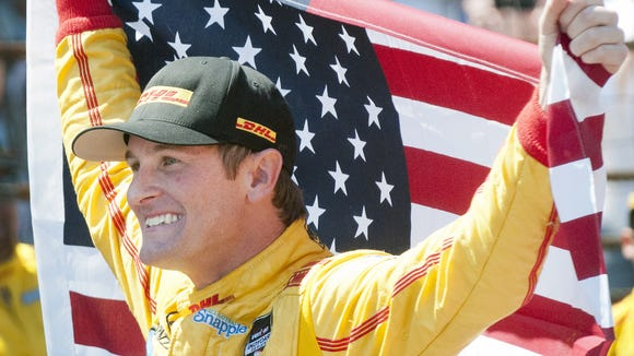 Ryan Hunter-Reay celebrates on the yard of bricks with an American flag after winning the 98th running of the Indianapolis 500 in 2014.