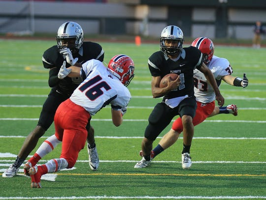 Busting through the Livonia Franklin defense Friday night is Plymouth quarterback Chris Walls (No. 21).