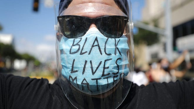 "A protester wears a face mask reading ""Black Lives Matter"" during a peaceful demonstration amid the coronavirus pandemic on June 6, 2020, in West Hollywood, California."