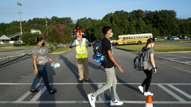Lakeside High School assistant principal Tim Reeve, in vest, holds traffic at a crosswalk as students make their way to school during the first day of classes Aug. 3 in Evans, Georgia.