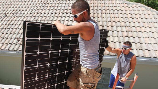 Kaleb Pambuena, left, and Brandon Schroder, of Fafco Solar, carry photovoltaic modules onto the roof of a home in the Island Walk development in Naples, as they prepare to install them.