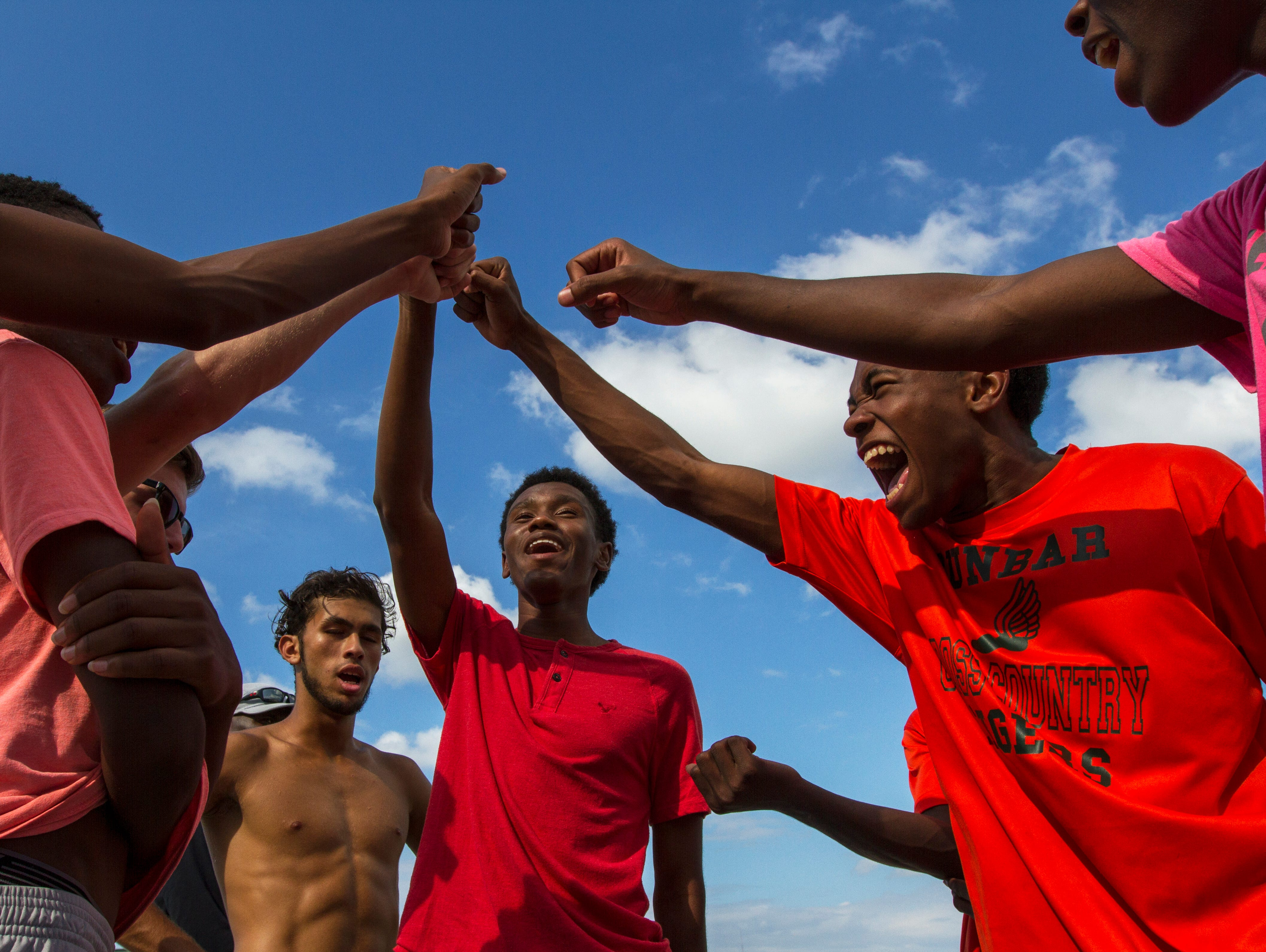 Members of the Dunbar High School cross country team chant in unity as they conclude their practice Wednesday, November 2, in Fort Myers. The cross country team has qualified for its first state championship in school history.