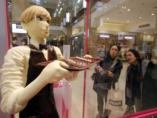 Shoppers admire a life sized cartoon character in a