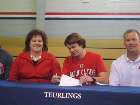 Josh Taylor with his parents and coach Mike Thibodeaux on National Signing Day