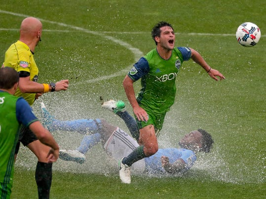 Seattle Sounders midfielder Nicolas Lodeiro (10) is tripped up by New York City FC defender Rodney Wallace (23) during the first half of a Major League Soccer game, Saturday, June 17, 2017, in New York. (AP Photo/Julie Jacobson)