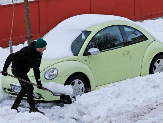 Ross Munroe digs out his car in Richmond, Va., on Jan.